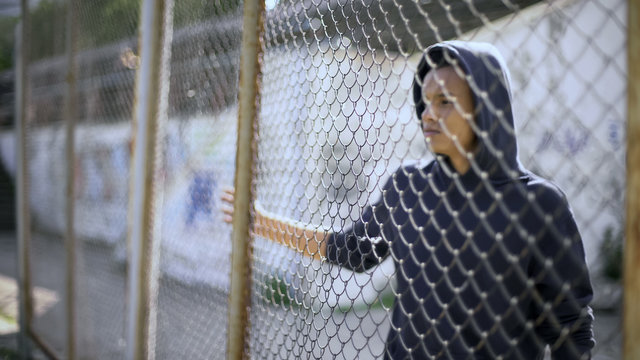 Migrant child separated from family, afro-american boy behind fence, detained
