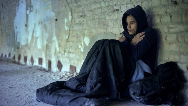 Upset homeless teenager wearing hoodie, feeling cold, indifference and poverty