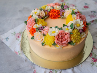 Yellow cream cake decorated with buttercream flowers - peonies, roses, chrysanthemums, carnations - on white wooden background. Card for March 8, Womens Day, Valentines Day. Copy space, Close up
