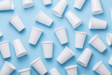 Single use white plastic cups on a blue background