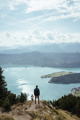Rear view of male hiker looking at lake while standing on mountain against cloudy sky during sunny day