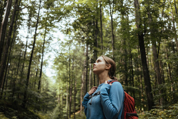Female hiker looking at view while standing in forest