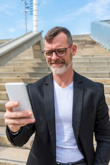 Confident businessman using smart phone while standing on steps against sky