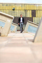 Surface level image of businessman walking on footpath against wall in city