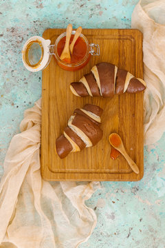 Overhead view of croissants with jam served on wooden tray