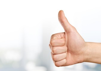 Closeup of male hand showing thumbs up sign against  background