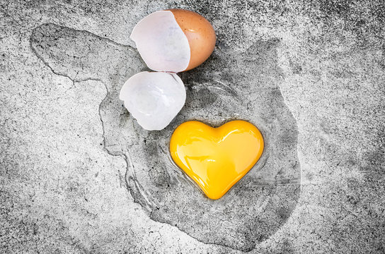 Heart Shape Egg Yolk with eggshells on the ground. Concept Valentines Day