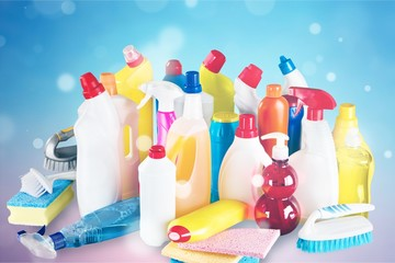 Plastic bottles, cleaning sponges and gloves on blue background