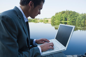 Businessman outdoors on wooden jetty using laptop by lake