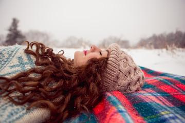 Side view of teenage girl sleeping on blanket in winter