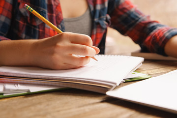 Midsection of teenage girl writing in notebook
