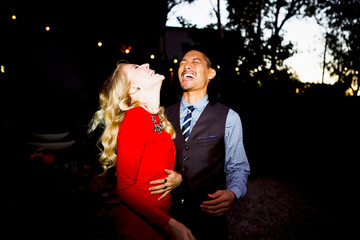 Multiethnic couple laughing while dancing during cocktail party in backyard at night