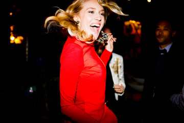 Woman in red dressing dancing at party
