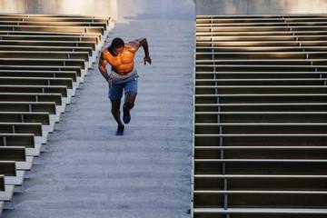 Full length of shirtless male athlete   running on steps at stadium