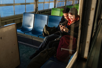 Smiling Couple Looking At Smartphone While Sitting In Ferry