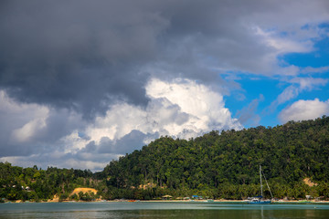 Tropical seaside landscape with sea water and greenery. Fishing boats and yacht in idyllic lagoon of tropical island.