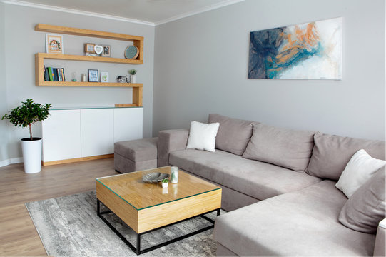 Grey corner couch with three pillows standing in bright living room interior with painting and carpet.Lightning off.