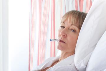 Female patient having temperature taken in hospital room looking at camera