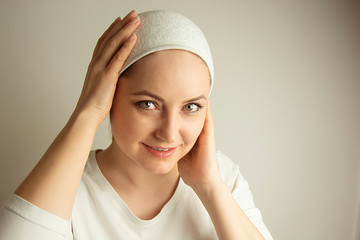 Skin care. Headshot of young woman with headband, getting face beauty procedures.