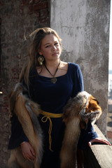 young woman in medieval dress and fox fur