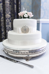 Wedding cake with white roses and jewel decoration