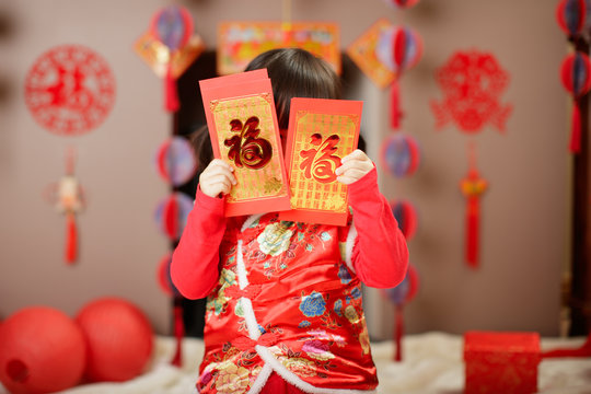 "Chinese baby girl  traditional dressing up with a FU means lucky red envelope against all kind of "" FU"" means"" lucky"" ornament and greeting card background"