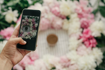 Hand holding phone and taking photo of peonies and coffee cup flat lay on rustic table cloth. Space for text. Blogging and instagram concept. Coffee in glass in peony frame top view on table