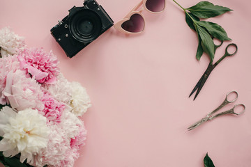 White and pink peonies, scissors, photo camera and sunglasses on pastel pink paper. Feminine flat lay with copy space. Hello spring image. Summer vacation. International Women's Day