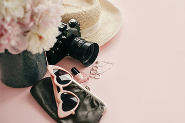 International Women's Day. Stylish girly image of pink peonies, photo camera, retro sunglasses, jewelry, nail polish, hat, purse on pastel pink paper with copy space.  Hello spring concept.