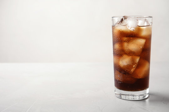 Glass of refreshing cola with ice on light table. Space for text