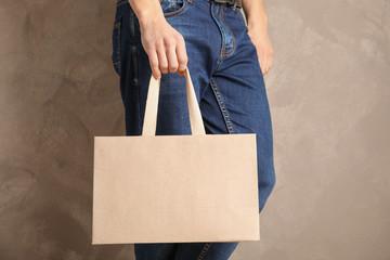 Man holding mock-up of paper shopping bag on color background