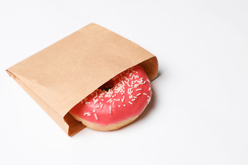 Paper bag with glazed doughnut on white background. Space for text