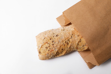 Paper bag with bread on white background, top view