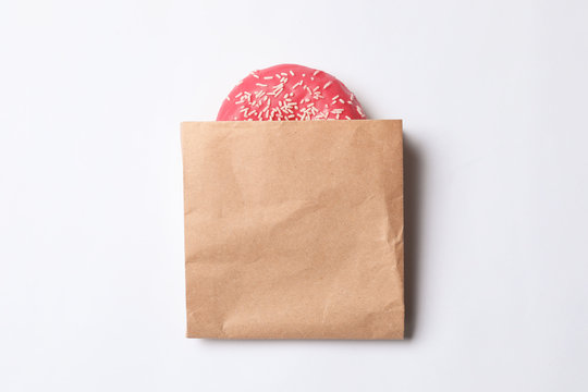 Paper bag with glazed doughnut on white background, top view. Space for design