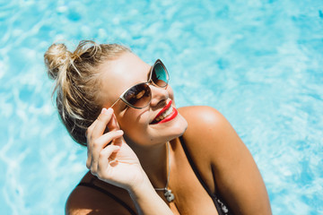 Young beautiful blonde woman in sunglasses with a good figure with red lips make-up posing in a pool of blue water. Outdoor portrait close up.
