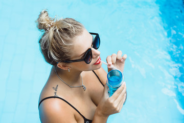 Young beautiful blonde woman in sunglasses with red lips make-up posing in a pool of blue water with a cocktail. Outdoor portrait close up.