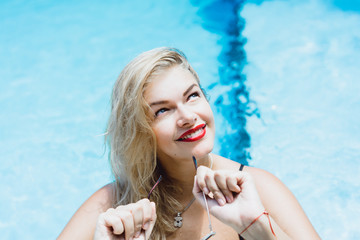Young beautiful blonde woman with sunglasses with a good figure with red lips make-up posing in a pool of blue water. Outdoor portrait close up.