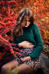 Beautiful pregnant woman posing on red tree leaf background.