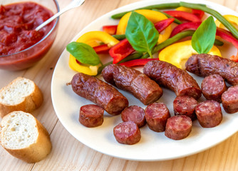 Grilled sausage on a plate on w wooden table