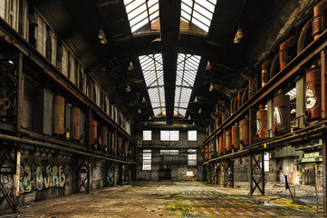 Symetric view of a abandoned and runied factory hall with glass roof