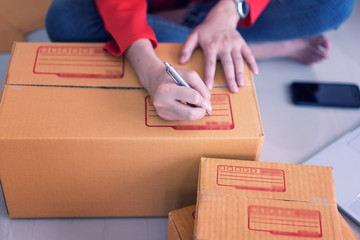 Woman sitting to check product details using mobile phones and computers.shopping online.The seller is packing the product in the box to deliver the product to the customer according to the order.