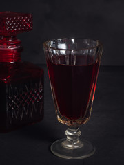 A glass of red wine, in the background a damask with wine. Picture taken on a dark background close-up.