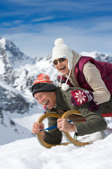 Laughing senior couple on winter vacation riding sled down mountain