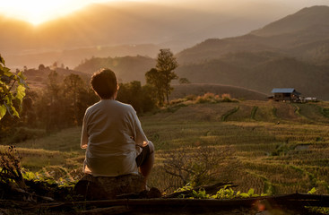 The back of senior woman watching the view rice field near mountain at Mae Chaem, Chiang Mai in time the sunset.