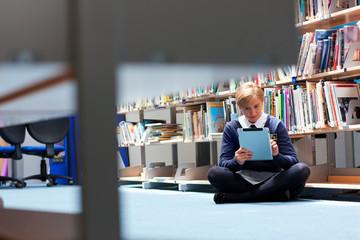 Male student in uniform using digital tablet in school library