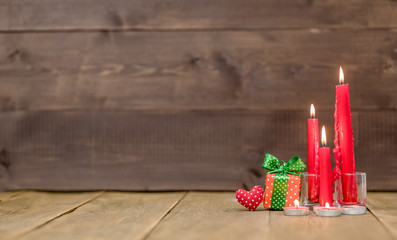 Gift boxes with candles on wooden background with empty space for text