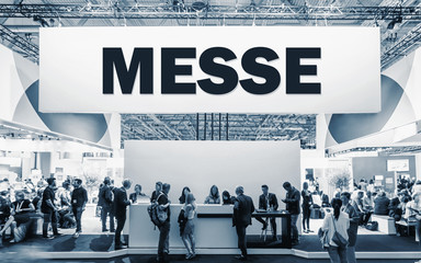 Fototapete - German text Messe, translate Trade Show. Crowd of people at a trade show booth with a banner and text
