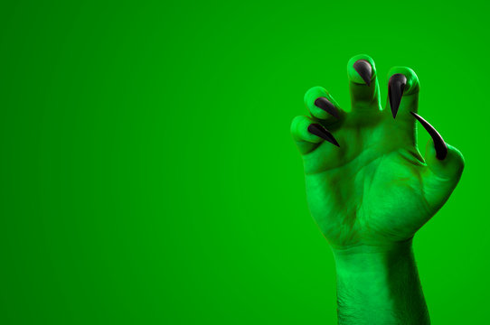 Halloween, nightmare creature and evil monster horror story concept with a scary zombie or demon hand with creepy long black nails isolated on green with a clip path cutout and copy space