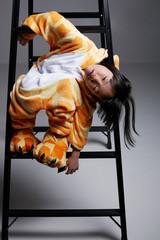 Asian little girl wearing giraffe pajamas, playing in the studio