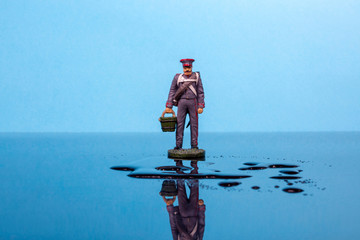 Tin soldier in the form of the Napoleonic Wars with a bucket stands in front of a puddle of water